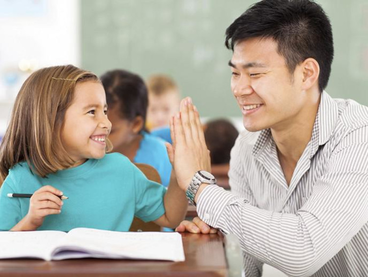 Male teacher gives younger female student a high five
