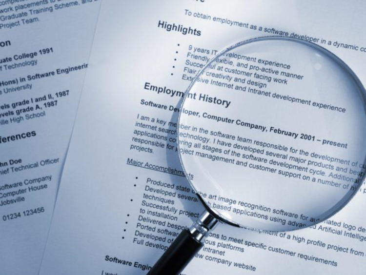A stack of resumes with a magnifying glass on top