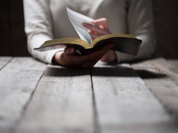 person flipping the page in a bible