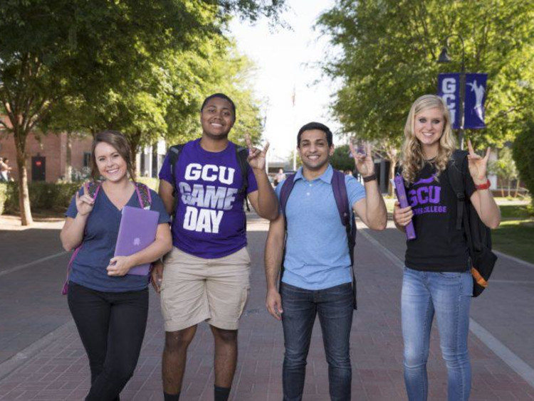 four students holding a lopes up