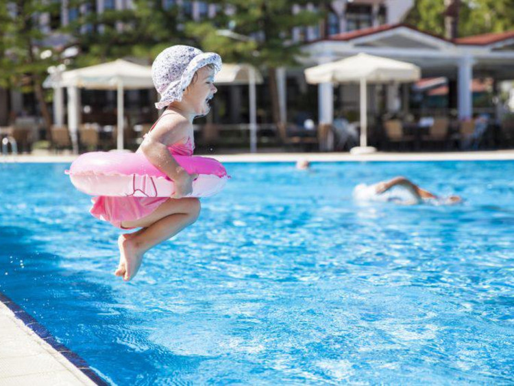 little girl jumping into a pool