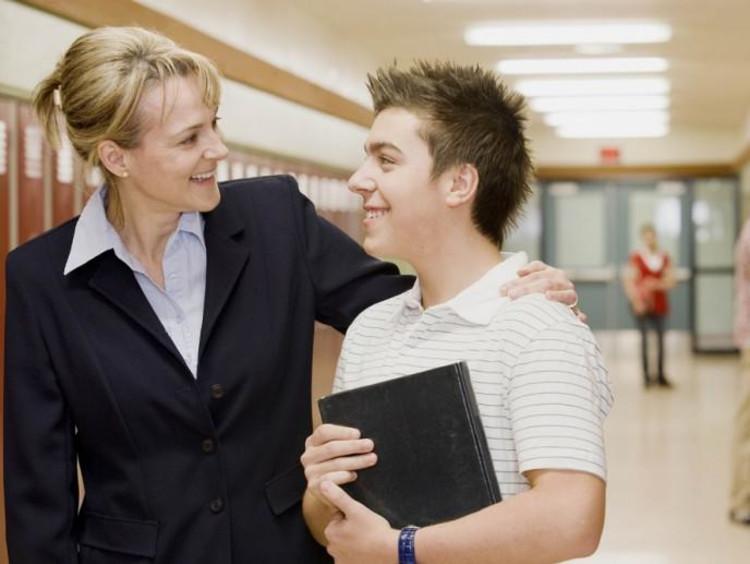 teacher with arm around student