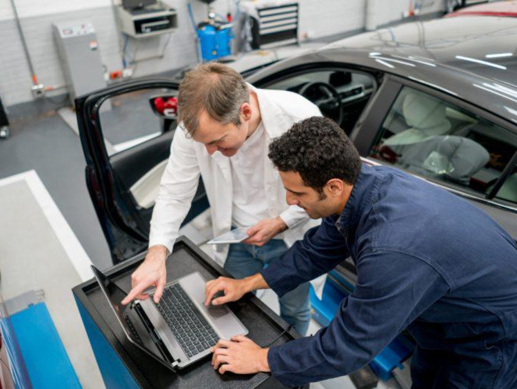 Man working on a computer by a car