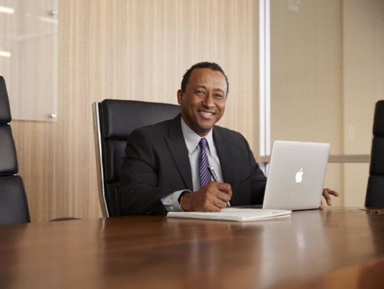 Smiling man in suit and tie sits in conference room with laptop open
