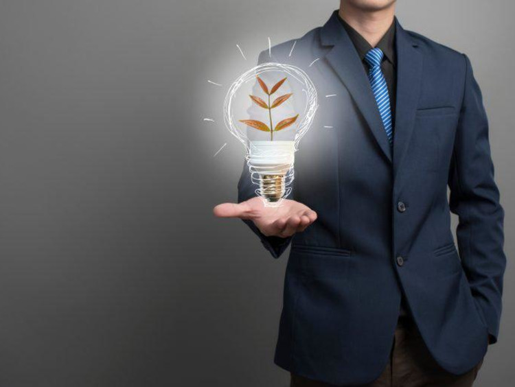 Midsection Of Businessman With Illustrative Bulb Standing Against Gray Background