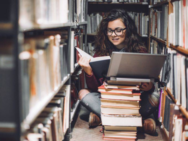 A female student researching in a library surrounded by books