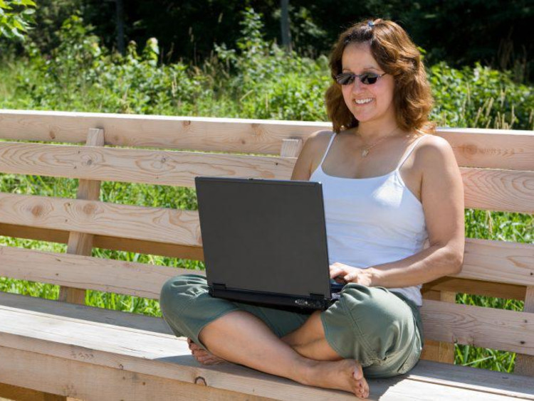 Doctoral student uses laptop in park