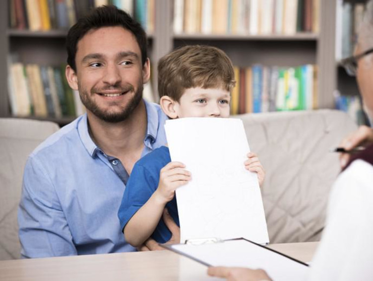 Father holds son who covers his face with papers while male counselor talks