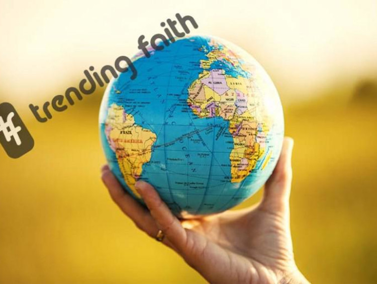 A hand holding a globe under the Trending Faith logo
