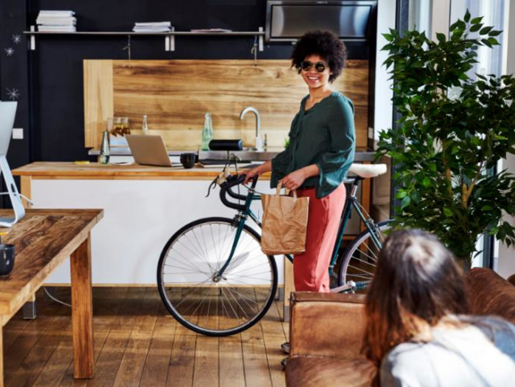 woman riding a bike to support sustainability efforts