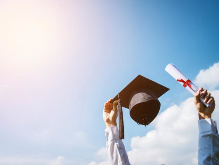 Man holding cap and diploma up in the sky