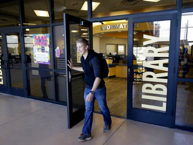 Male student walks out of library entrance