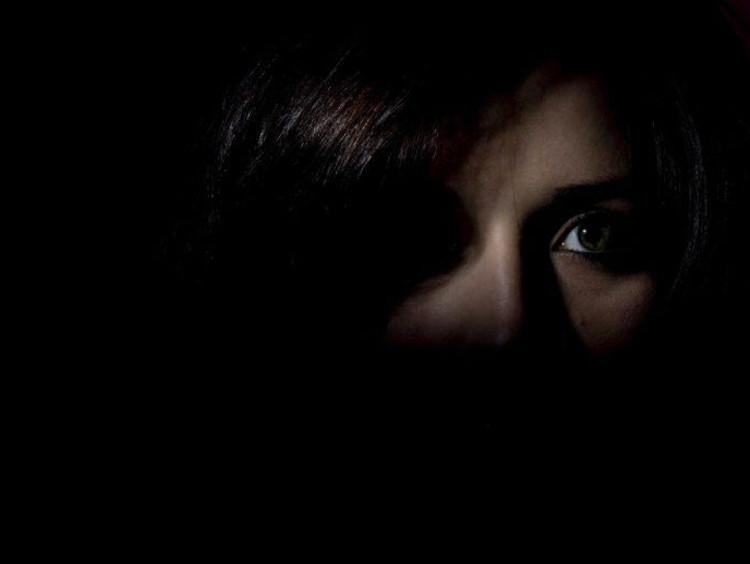 A person's face hiding in the shadows