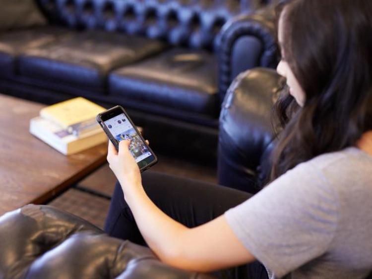Brunette female uses left hand to scroll social media app in living room