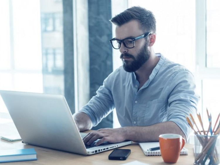 Bearded male sits at desk and uses laptop