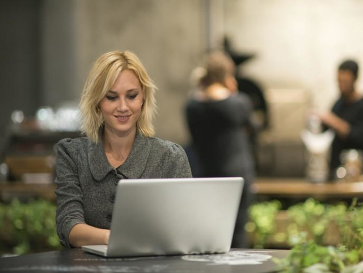 Blonde professional woman typing on her computer