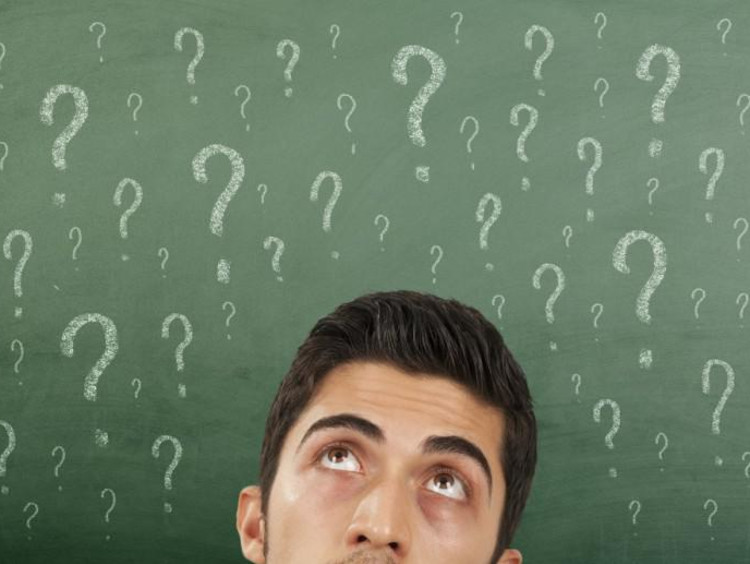 question marks on a chalkboard and person thinking
