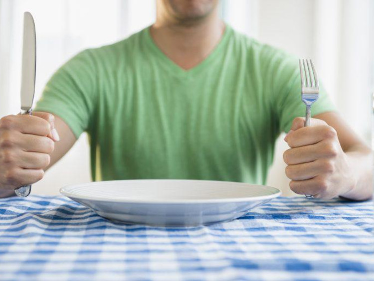 Man sitting in front of an empty plate