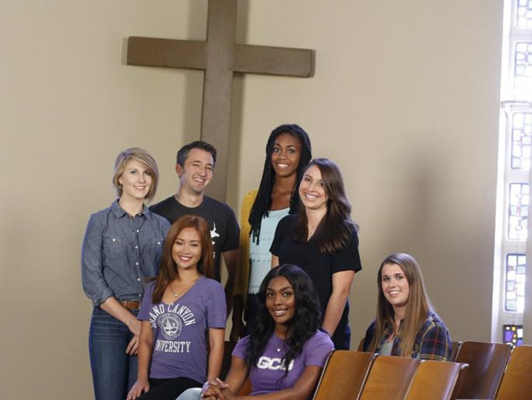 group of GCU students standing in front of cross and smiling