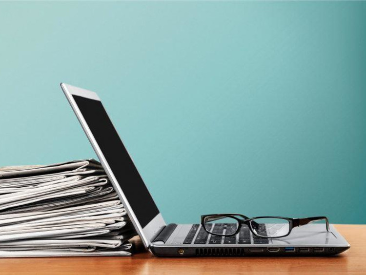 Laptop propped up on a stack of papers