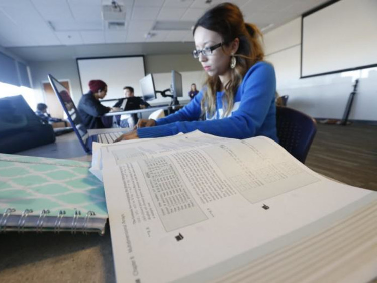 Student review textbooks in library setting