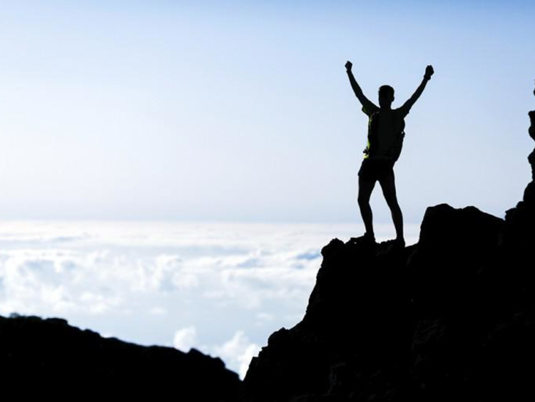 Man stands on top of mountain cliff raising hands in triumph