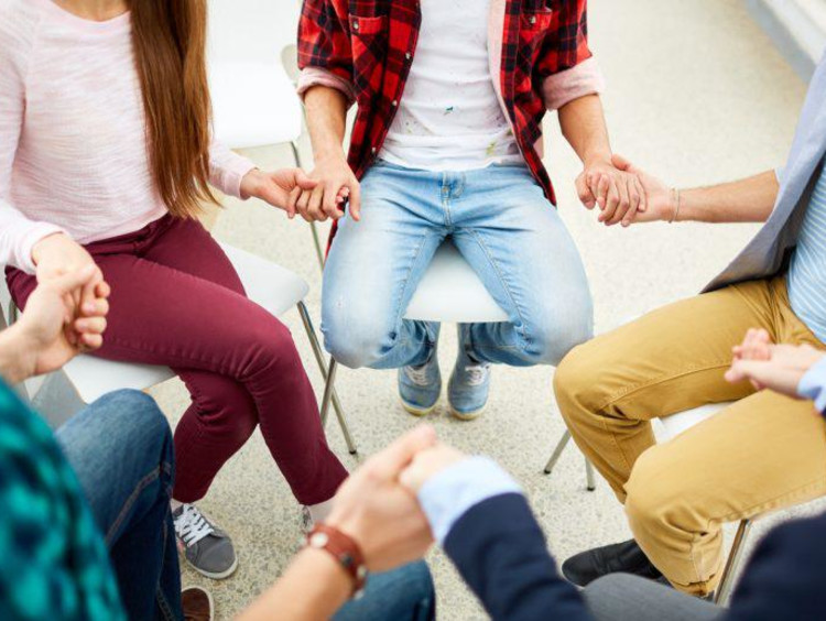 people sitting in a circle and holding hands