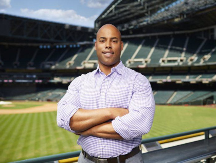 man in a dress shirt standing in front of a stadium
