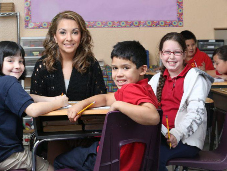 Female teacher sitting with students