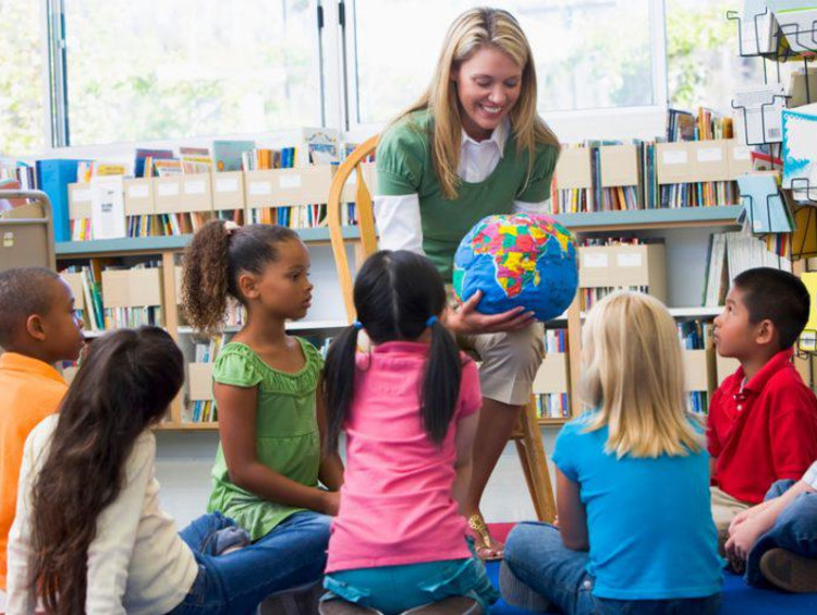 teacher showing a globe to young students