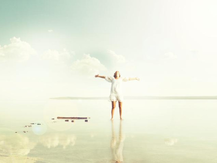 A woman walking joyfully on reflective water