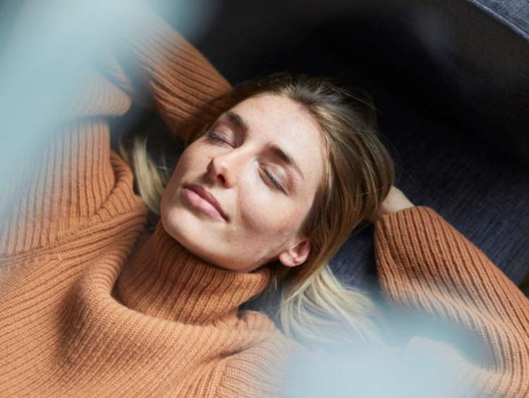 Woman contentedly smiling with eyes closed