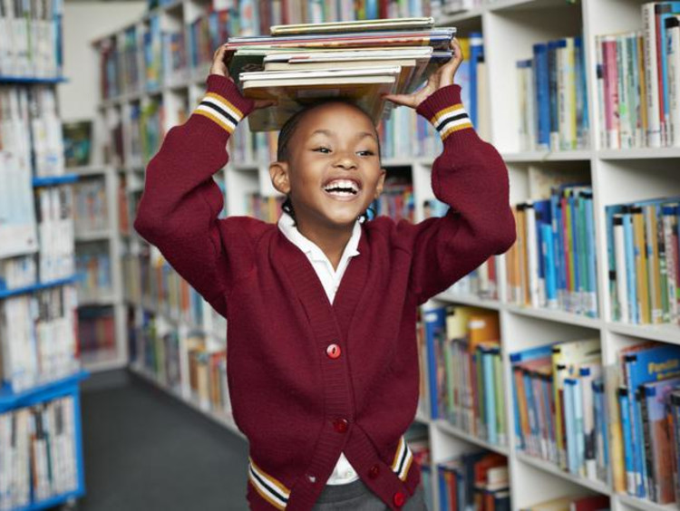 Girl stacks thin books atop her head in library