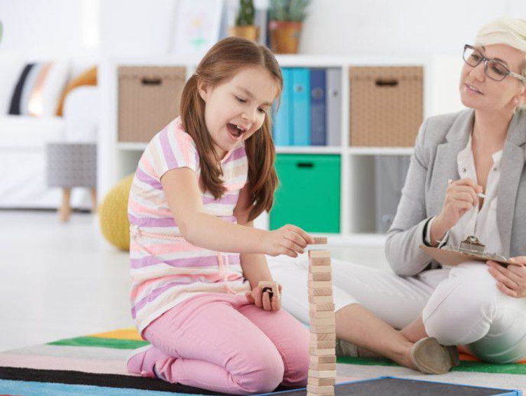 Child counselor sits on floor and observes a little girl playing with wood blocks