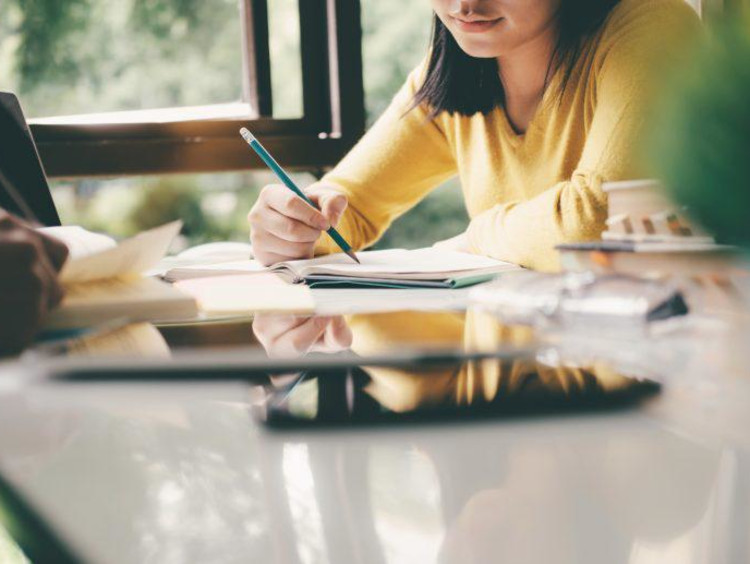 Midsection Of Woman Reading Book While Sitting At Table