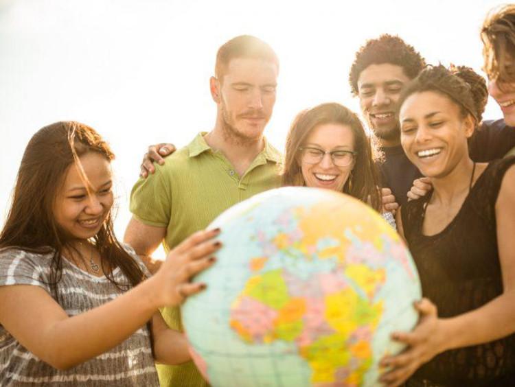 International students gathered around a globe