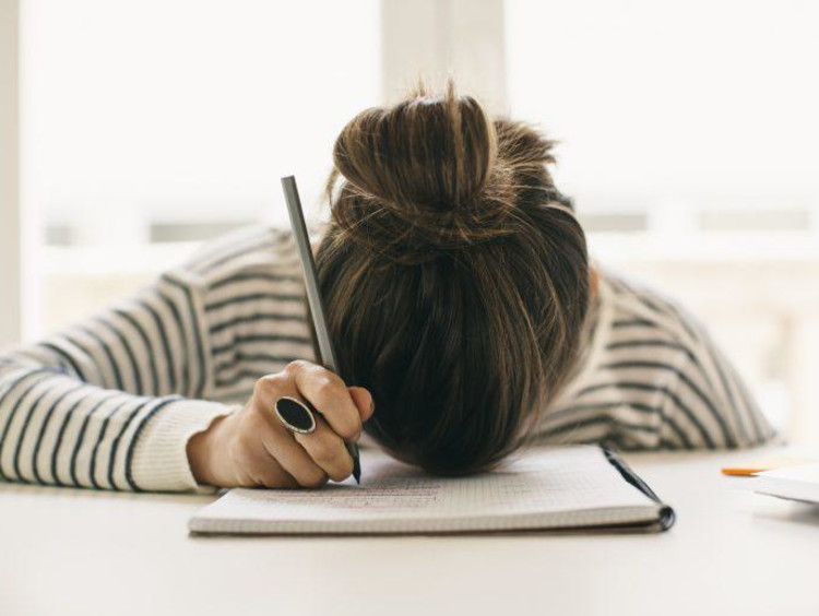 Overwhelmed student with her head on her desk