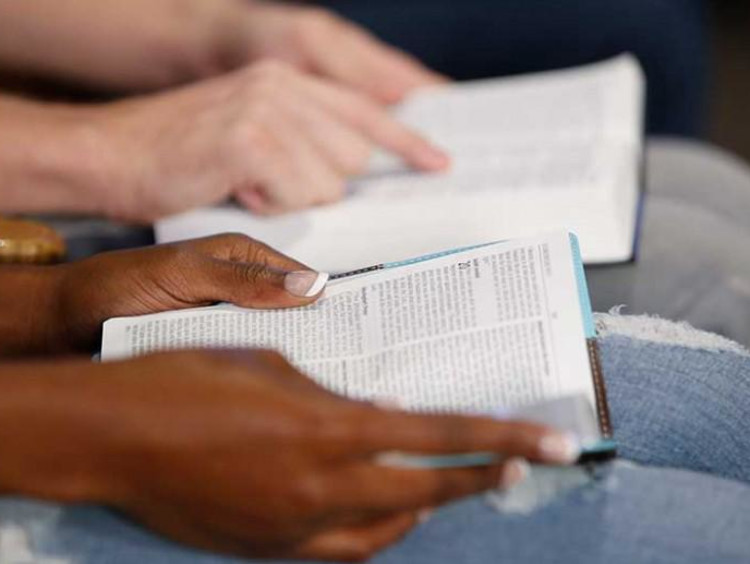 Close view of bibles opened on couples lap as they follow along