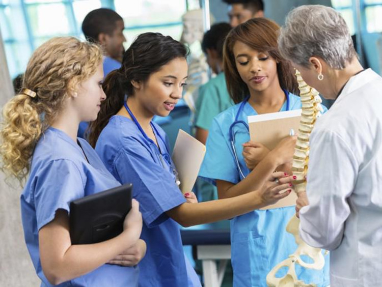 three nursing students and professor looking at a skeleton