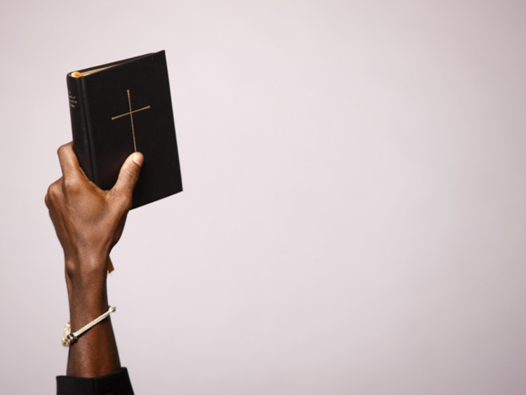 Holding a Bible Up in one hand