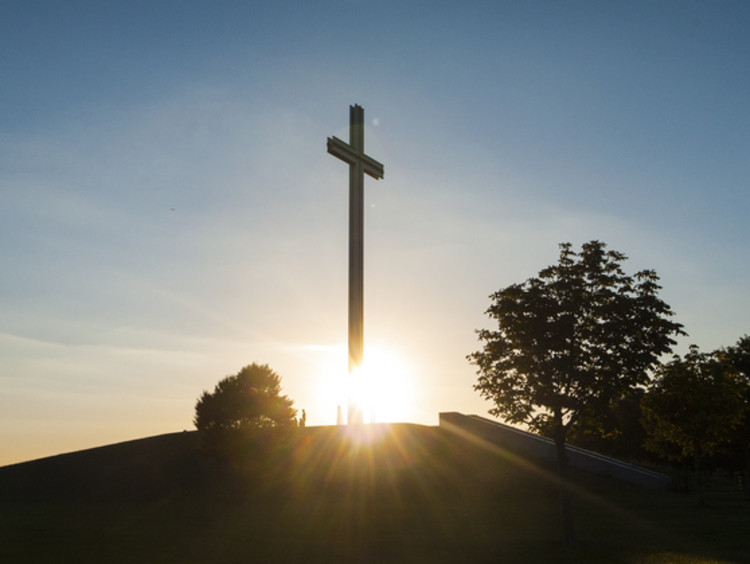 cross on a hill in front of the sun rising