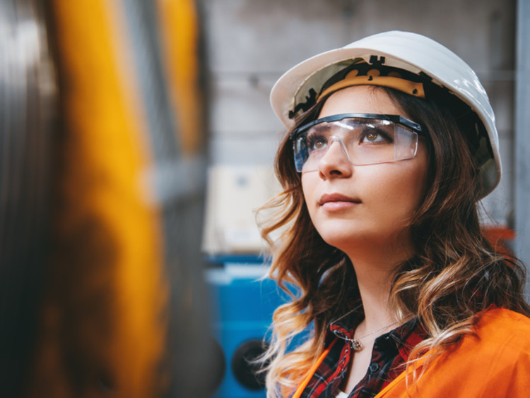 girl in hard hat and safety glasses at a construction site