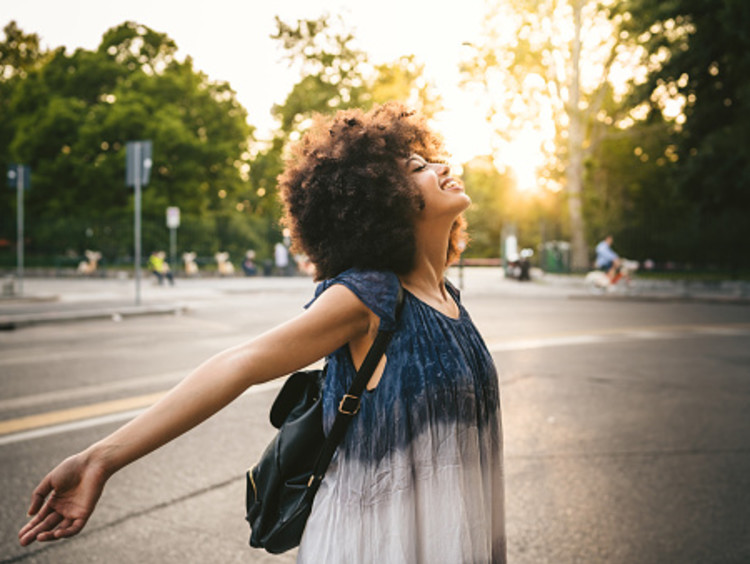 Curly-haired woman has arms open enjoying the sunlight in an empty parking lot