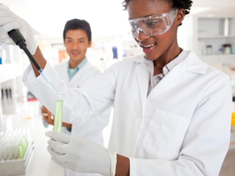 African-American female scientist putting a solution in test tube to use scientific method in a lab
