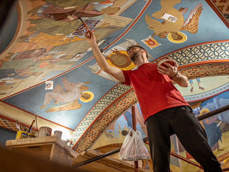 Man wearing red shirt using his gifts from God to repair Christian artwork on church ceiling