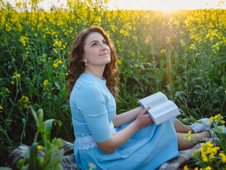 Woman looking up after reading her Bible in a field of flowers for spiritual cleansing