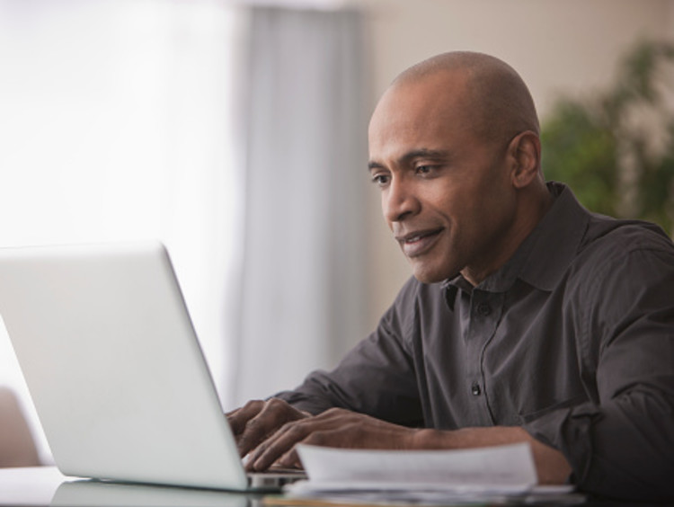 Professor replying to emails on laptop