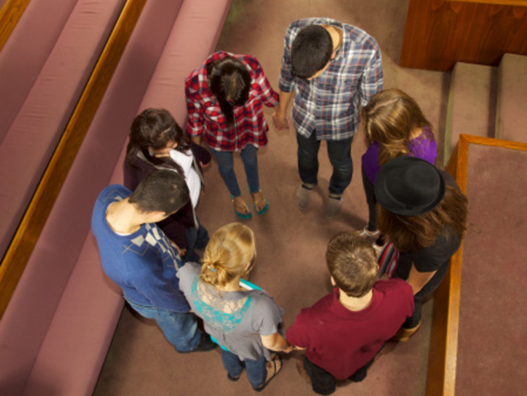 Christians standing and holding hands while praying for one another near church pews