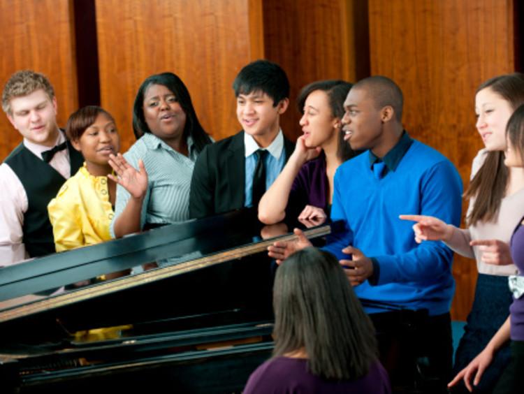 African-American male worship leader in blue shirt leading an interracial choir around a black piano