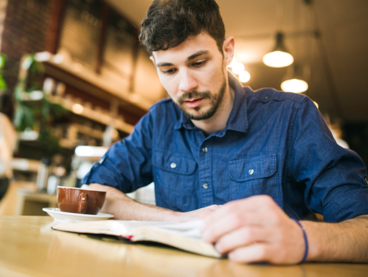 Man reading his Bible in a coffee shop